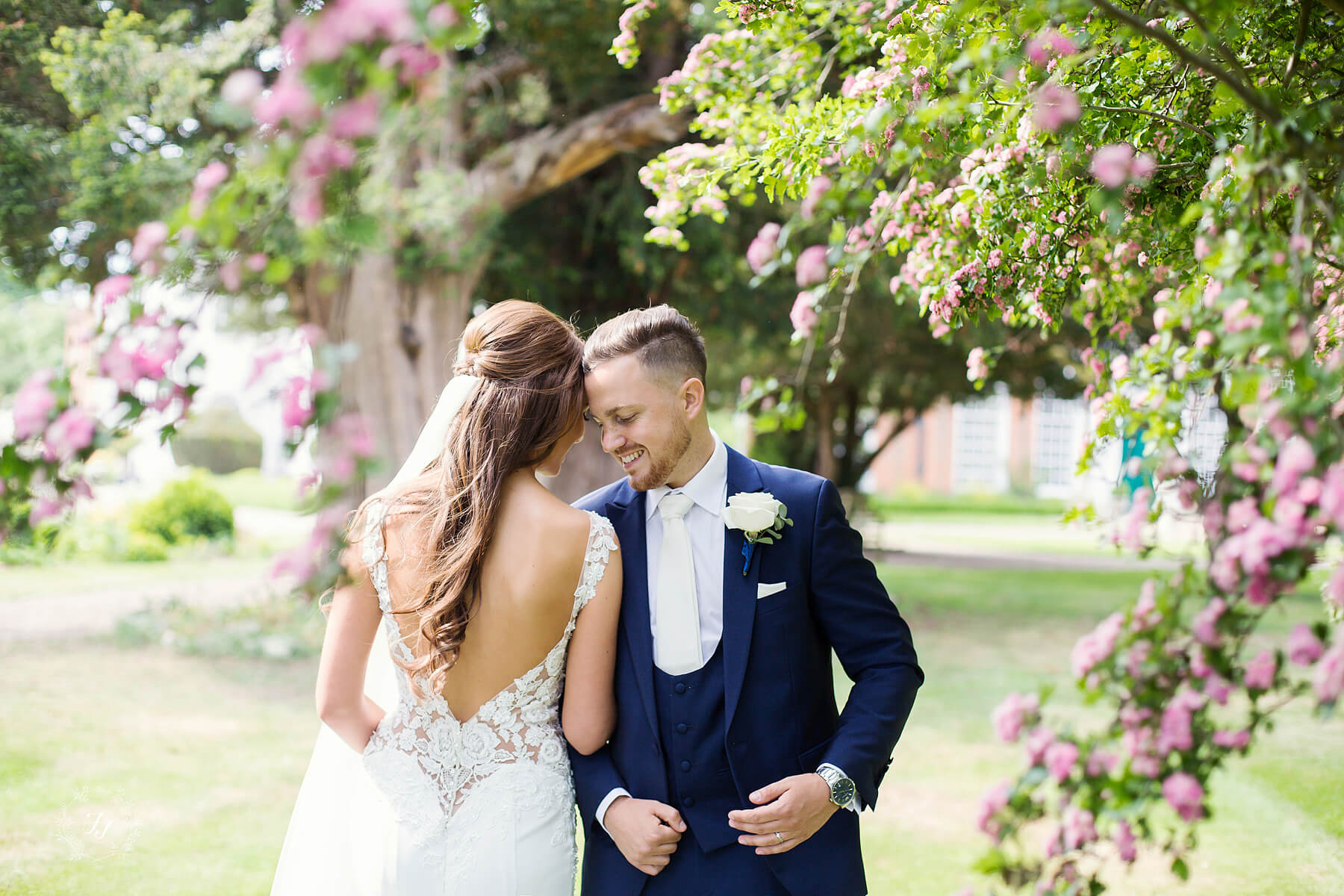 bride and groom photographed in the rose garden at Gosfield Hall