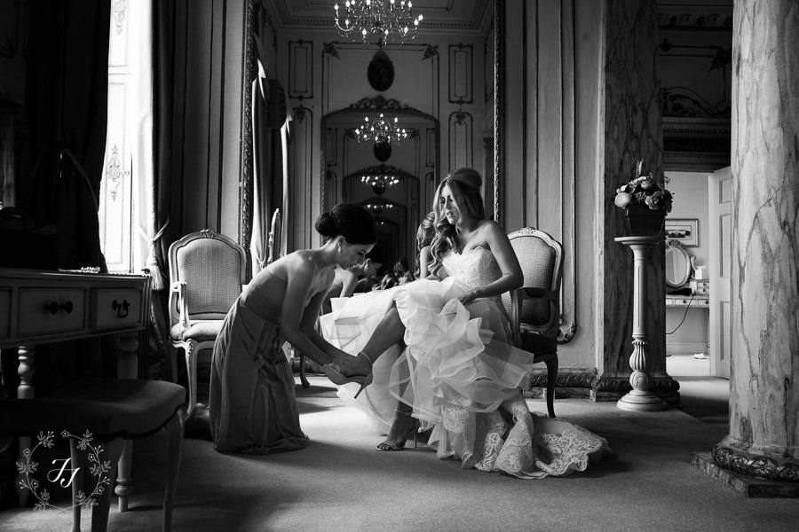 bridesmaid putting on brides shoe in bridal suite at Gosfield Hall