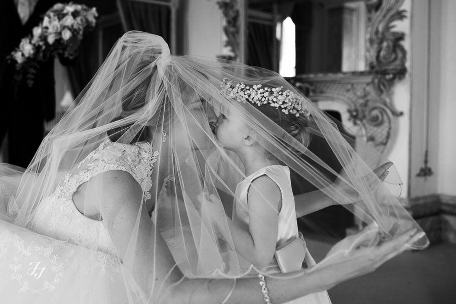 flower girl and bride kiss under veil
