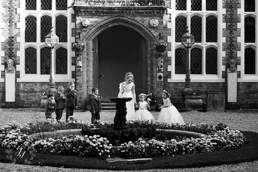children looking at water fountain in Gosfield Halls courtyard at autumn wedding