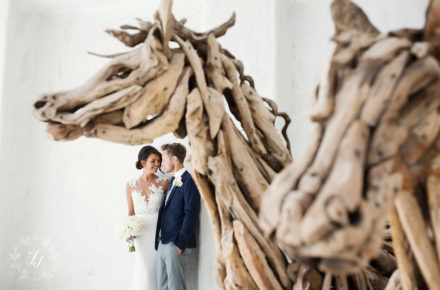 Stacey and Sam's wedding in Mykonos in the royal Myconian Hotel standing by wicker horses wearing a pronovias wedding dress