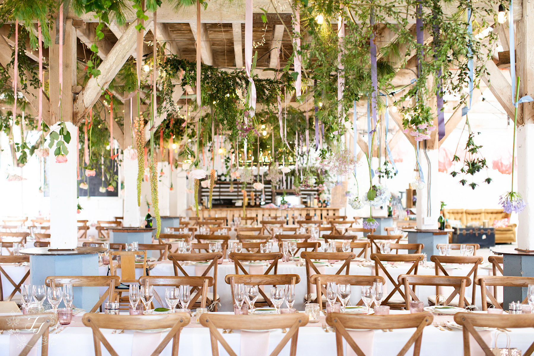 long tables at the railway barn in Purleigh essex flowers hanging from ceiling