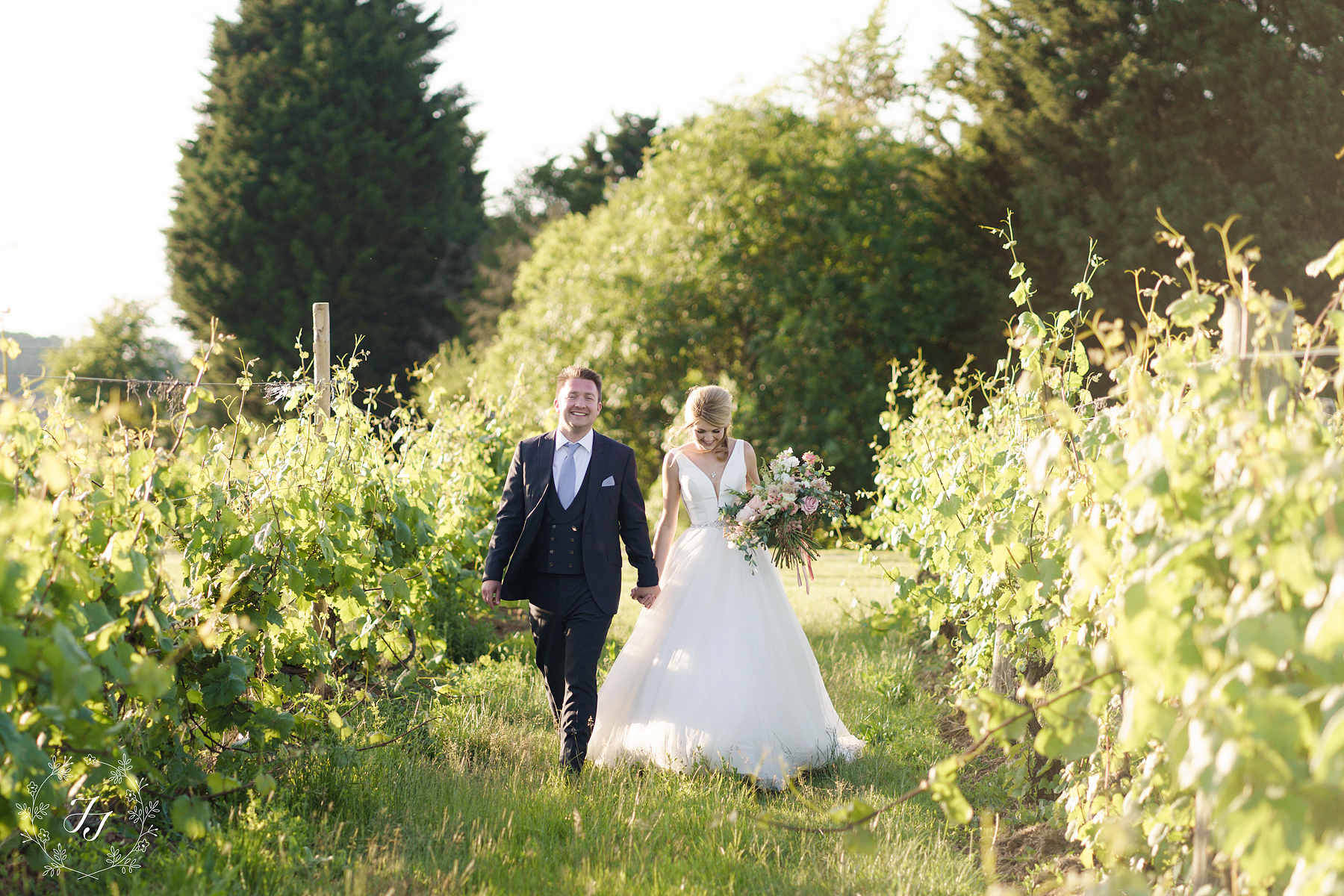 wedding photography at Newhall vineyard, bride and groom walk through the vineyard