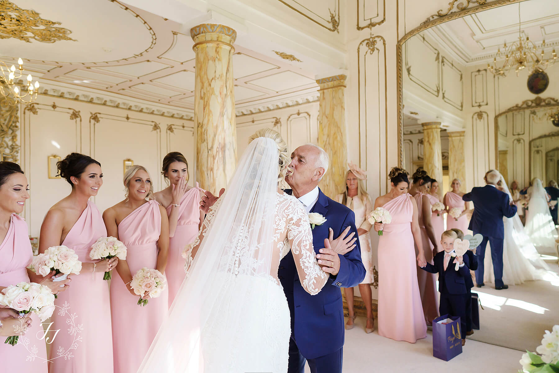 father of the bride kissing bride and blush pink bridesmaids reaction