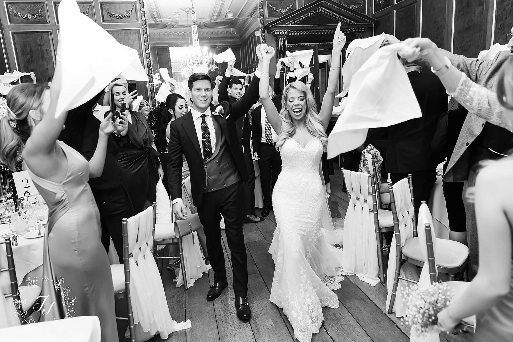 the bride and groom enter the ballroom and the guest are all cheering as they are announced
