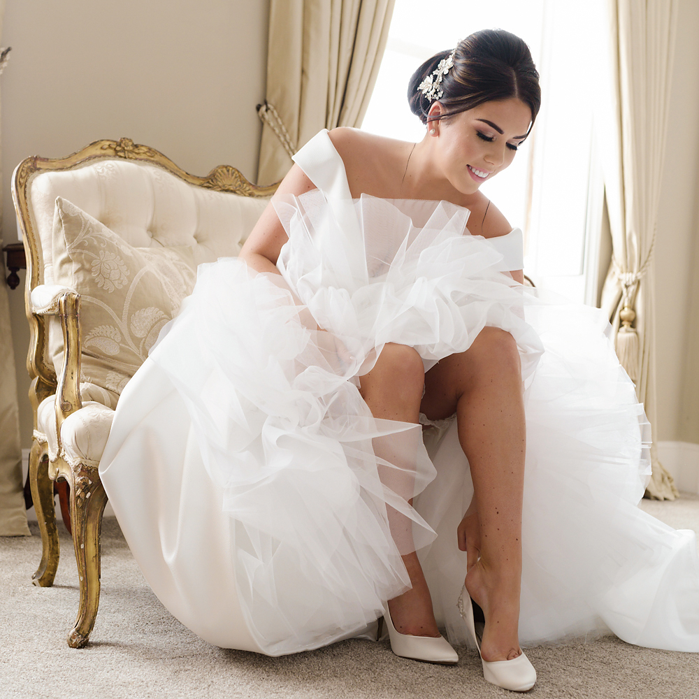 Jordan putting on her wedding shoes for her Hatfield Place wedding
